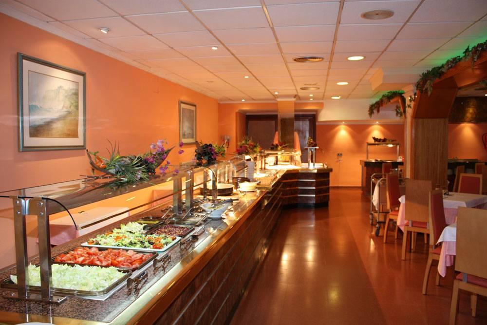 Zona tipo buffet con cocina vista, mesa de frutas, helados y pastelería propia.